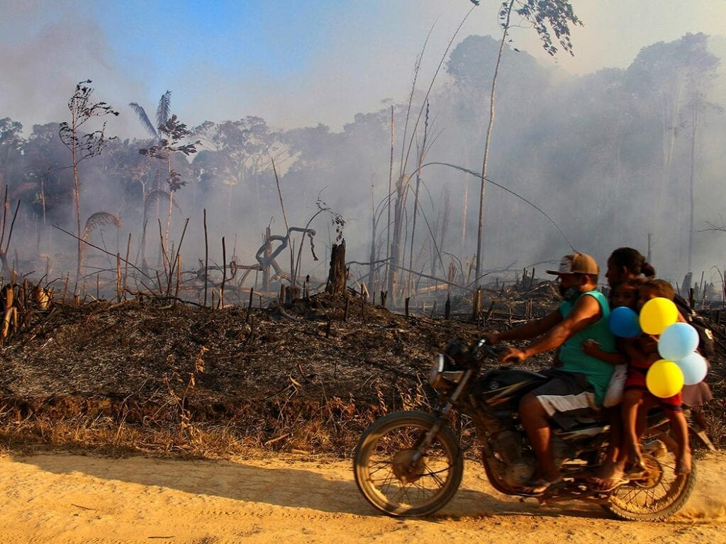 A family rides along a paved dirt road in an area scorched by fires near Labrea, Amazonas state, Brazil
