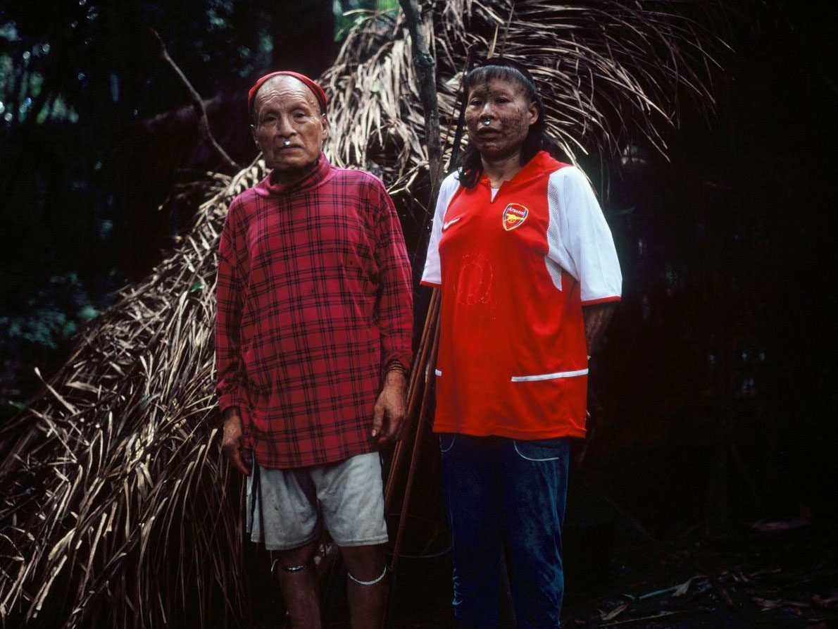 Shuri and wife Janet stand in front of their palm-thatched shelter, or maloca, in May 2017